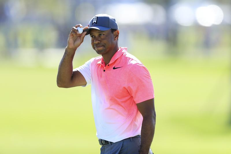 Tiger Woods doffs his hat to the crowd on the ninth hole after holing a 24-foot birdie putt in the second round of the Honda Classic. (Photo by Sam Greenwood/Getty Images)