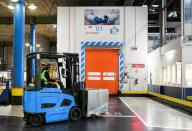 A KLM worker is entering a cold room by a forklift truck at Amsterdam's Schiphol Airport