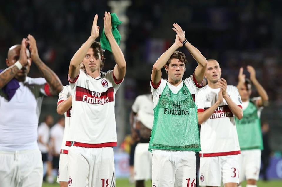 AC Milan's Nigel de Jong (L), Riccardo Montolivo (C) and Andrea Poli greet fans at the end of their Serie A match against Fiorentina at the Florence stadium on August 23, 2015 in Florence (AFP Photo/Massimo Benvenuti)