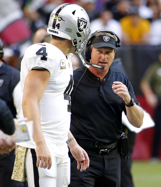 Oakland Raiders head coach Jon Gruden talks with quarterback Derek Carr (4) during the first half of an NFL football game against the Arizona Cardinals, Sunday, Nov. 18, 2018, in Glendale, Ariz. (AP Photo/Rick Scuteri)