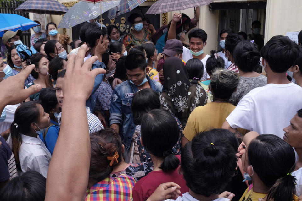 A man, rear, smiles amidst a waiting crowd as he steps out of Insein prison in Yangon, Myanmar Saturday, April 17, 2021. Myanmar's junta on Saturday announced it pardoned and released more than 23,000 prisoners to mark the new year holiday, but it wasn't immediately clear if they included pro-democracy activists who were detained in the wake of the February coup. (AP Photo)
