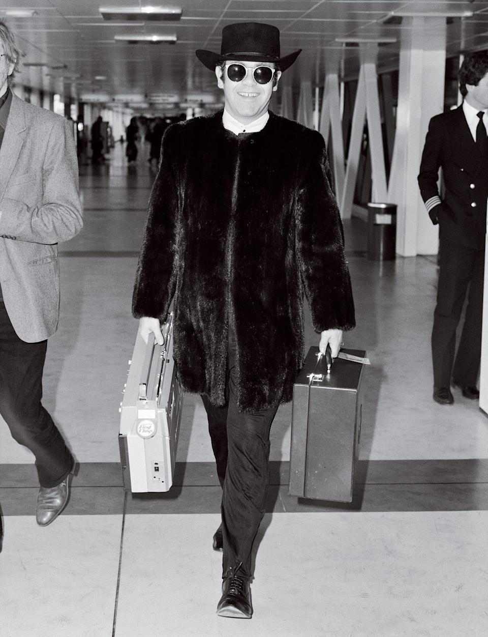 <p>The Rocket Man accessorized with a boom box en route to the Concorde (his preferred method of crossing the Atlantic until the planes were retired in 2003) for a flight from London's Heathrow to N.Y.C.</p>