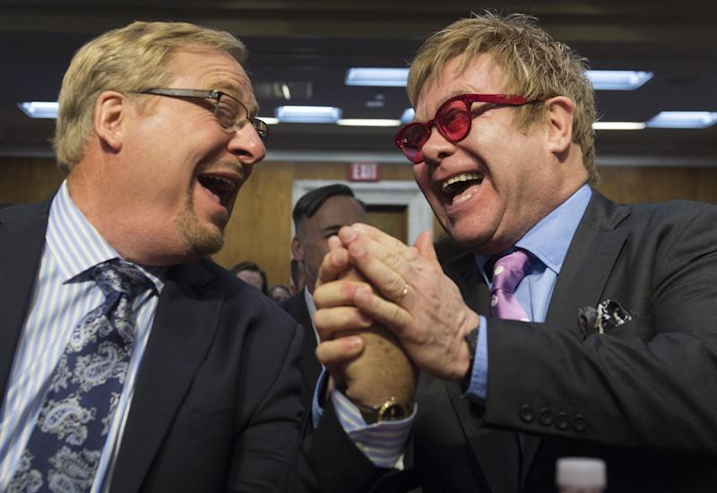 Singer Elton John (right), founder of the Elton John AIDS Foundation, and Pastor Rick Warren (left) of the Saddleback Church, arrive to testify about global health programs during a Senate Appropriations Subcommittee hearing on Capitol Hill on May 6, 2015.