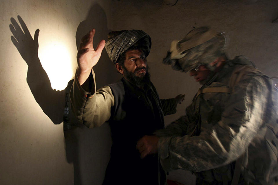 A U.S. soldier of B company, 4th Infantry Regiment frisks an afghan man in his house during a search operation in Sinan village in Zabul province, southeastern Afghanistan, Monday, April 2, 2007. (AP Photo/Rafiq Maqbool)