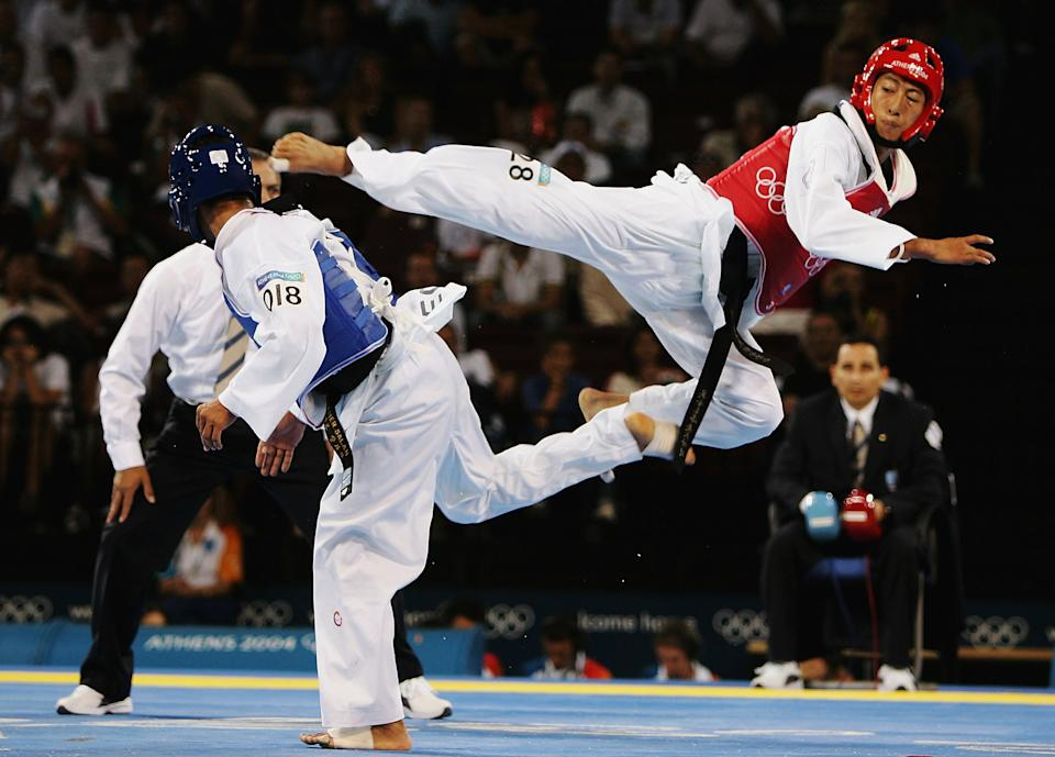 ATHENS - AUGUST 26:  Mu Yen Chu of Chinese Taipei jumps up for a kick against Tamer Bayoumi of Egypt in the men's under 58 kg Taekwondo preliminary match on August 26, 2004 during the Athens 2004 Summer Olympic Games at the Sports Pavilion part of the Faliro Coastal Zone Olympic Complex. (Photo by Al Bello/Getty Images)