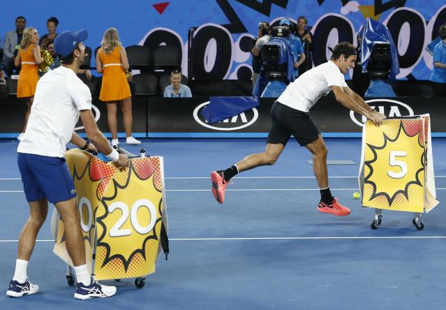 Tennis - Australian Open - Rod Laver Arena, Melbourne, Australia, January 13, 2018. Novak Djokovic of Serbia and Roger Federer of Switzerland catch balls hit by Milos Raonic of Canada during Kids Tennis Day before the Australian Open tennis tournament. REUTERS/Thomas Peter