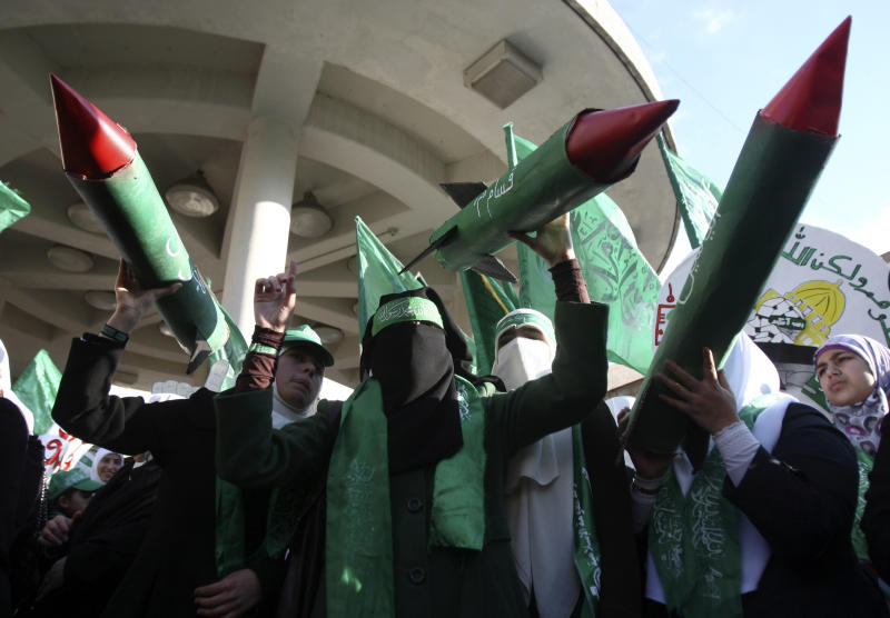 Palestinian supporters of Hamas hold models of M75 long-range rockets during a rally to celebrate the 25th anniversary of the Hamas militant group, in the West Bank city of Nablus, Thursday, Dec. 13, 2012. Hamas supporters rallied in the first display of force by the Islamic militant group in the West Bank since it overran Gaza from the Western-backed party of Palestinian President Mahmoud Abbas in 2007. (AP Photo/Nasser Ishtayeh)