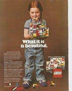 Young girl in overalls, holding lego blocks.