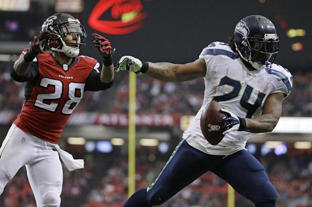 Seattle Seahawks running back Marshawn Lynch (24) scores a touchdown against Atlanta Falcons free safety Thomas DeCoud (28)during the second half of an NFL football game, Sunday, Nov. 10, 2013, in Atlanta. (AP Photo/David Goldman)