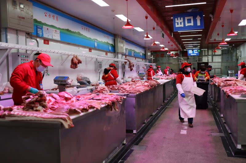 Vendors sell pork at the Xinfadi wholesale market in Beijing