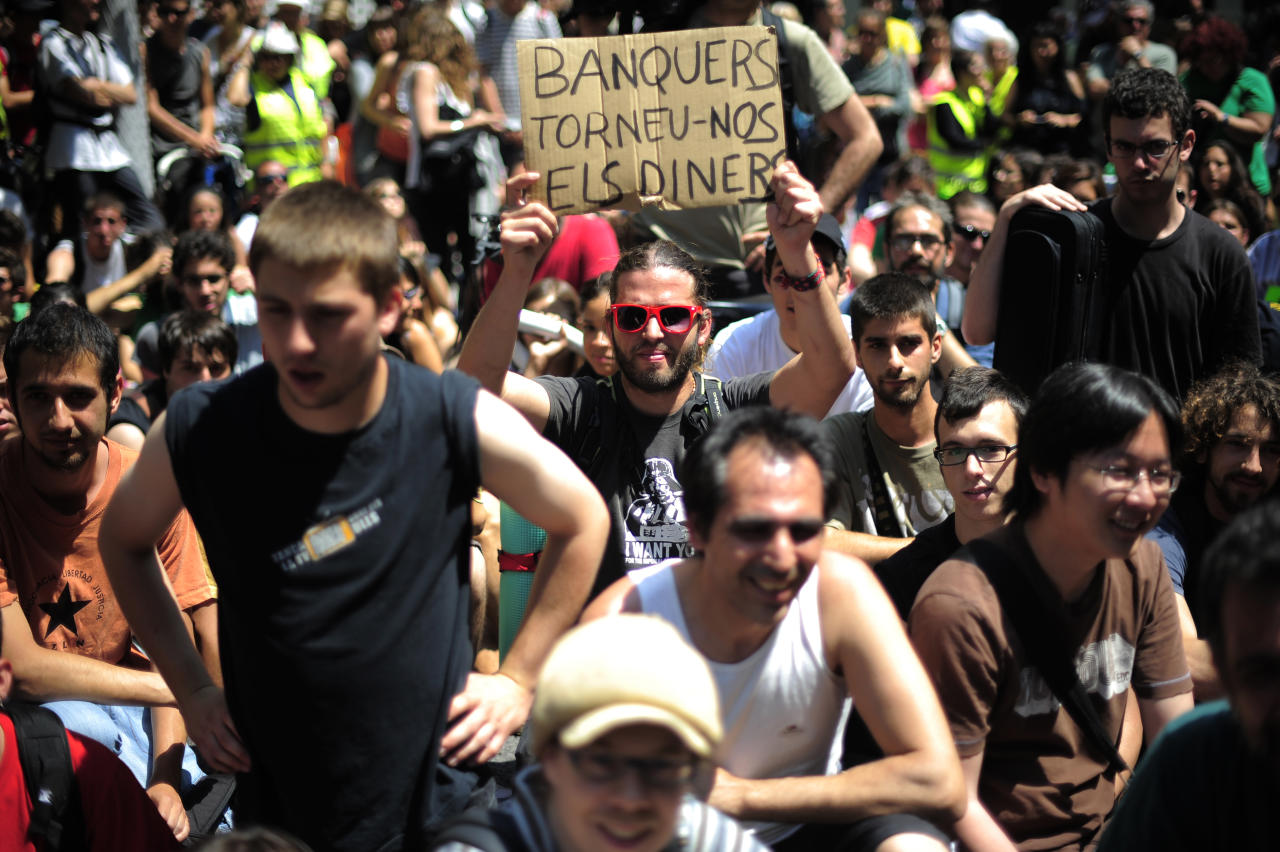 "Protesters are seen during a demonstration against austerity cuts in Barcelona, Spain, Tuesday, May 15, 2012. Spain got caught up in the uncertainty surrounding the European single currency and the electoral stalemate in Greece Monday as it saw its borrowing costs rise and stock prices fall at alarming rates. The banner reads in Catalan: ""Bankers return the money"". (AP Photo/Manu Fernandez)"