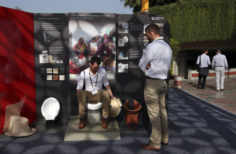In this Friday, March 21, 2014 photo, an exhibitor from Loughborough University demonstrates the use of a toilet during Reinvent The Toilet Fair in New Delhi, India. Scientists who accepted the Bill & Melinda Gates Foundation's challenge to reinvent the toilet showcased their inventions in the Indian capital Saturday. The primary goal: to sanitize waste, use minimal water or electricity, and produce a usable product at low cost. India is by far the worst culprit, with more than 640 million people defecating in the open and producing a stunning 72,000 tons of human waste each day - the equivalent weight of almost 10 Eiffel Towers or 1,800 humpback whales. (AP Photo/Tsering Topgyal)