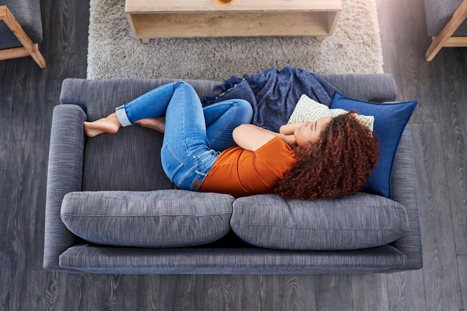 Shot of a young woman lying on the sofa at home and looking depressed