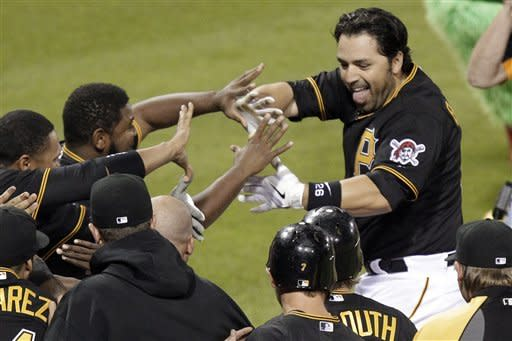 Pittsburgh Pirates' Rod Barajas, top right, is greeted by teammates after hitting a two-run home run off Washington Nationals pitcher Henry Rodriguez in the ninth inning of a baseball game in Pittsburgh Tuesday, May 8, 2012. The Pirates won 5-4. (AP Photo/Gene J. Puskar)