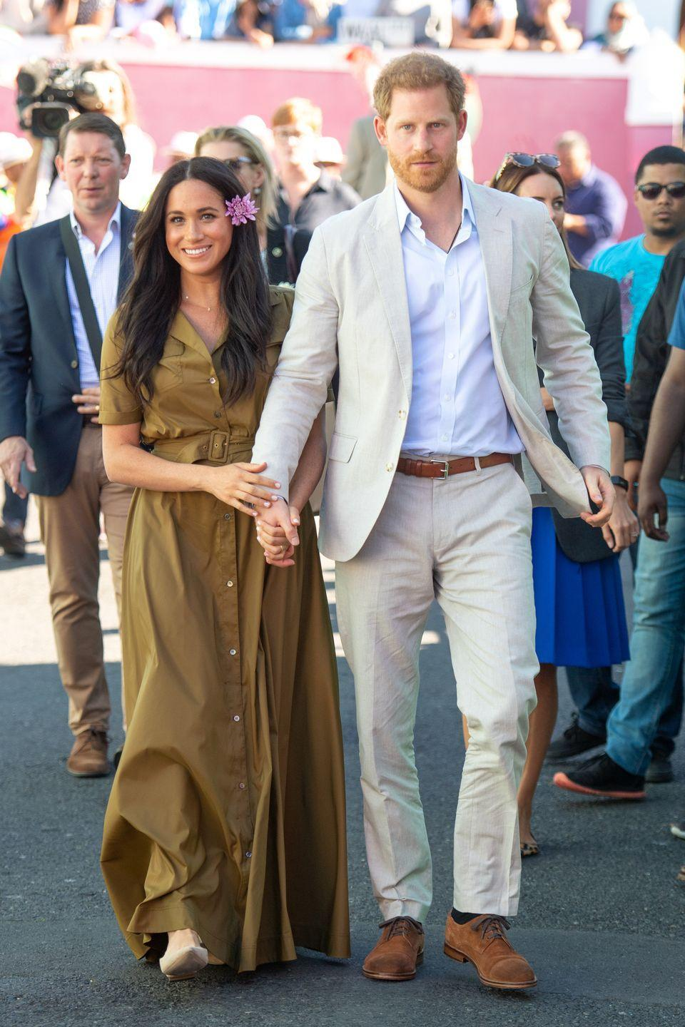 <p>Meghan held Prince Harry's hand tightly at they walked through the Bo Kaap district of Cape Town, during the royal tour of South Africa on 24 September. </p>