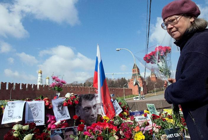 A woman lays flowers on April 7, 2015 at the site in central Moscow where Russian opposition leader Boris Nemtsov was shot dead (AFP Photo/Alexander Utkin)