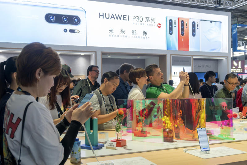 "Visitors look at a display of smartphones from Chinese technology firm Huawei at the Consumer Electronics Show in Shanghai, Tuesday, June 11, 2019. Chinese tech giant Huawei said Tuesday it would have become the world's number one smartphone maker by year's end if it were not for ""unexpected"" circumstances — a hint that pressure from the U.S. may be hurting its sales. (Chinatopix via AP)"