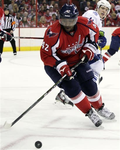 Washington Capitals right wing Joel Ward (42) goes for the puck as Toronto Maple Leafs right wing Nikolai Kulemin looks on during the second period of an NHL hockey game on Sunday, March 11, 2012, in Washington. (AP Photo/Carolyn Kaster)