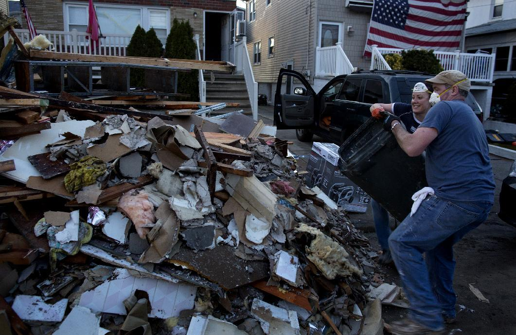 Volunteer Ashling Coleman and her husband Jerry Coleman of New York throw out the last load of debris for the day from the home of John and Ann Garvey, background left, which was damaged in the Rockaway Park neighborhood in the Queens borough of New York, Sunday, Nov. 11, 2012, from Superstorm Sandy. The Colemans, bringing other family members with them, came to the neighborhood today just to see if they could find anyone who needed help. They found the Garvey's home, offered their assistance, and were gladly welcomed in. (AP Photo/Craig Ruttle)