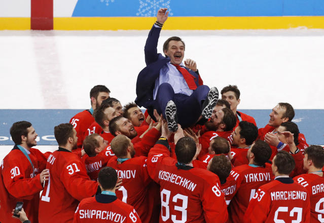 Olympic athletes from Russia celebrate with their coach Oleg Znarok after winning the men's gold medal hockey game against Germany, 4-3, in overtime at the 2018 Winter Olympics, Sunday, Feb. 25, 2018, in Gangneung, South Korea. (AP Photo/Jae C. Hong)