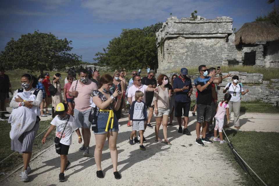 Tourists, required to wear protective face masks amid the new coronavirus pandemic, visit the Mayan ruins of Tulum in Quintana Roo state, Mexico, Tuesday, Jan. 5, 2021. More U.S. tourists came to Quintana Roo during this pandemic-stricken holiday season than did a year earlier when the world was just beginning to learn of COVID-19. They account for 9 out of 10 foreign tourists, said state Tourism Secretary Marisol Vanegas. (AP Photo/Emilio Espejel)