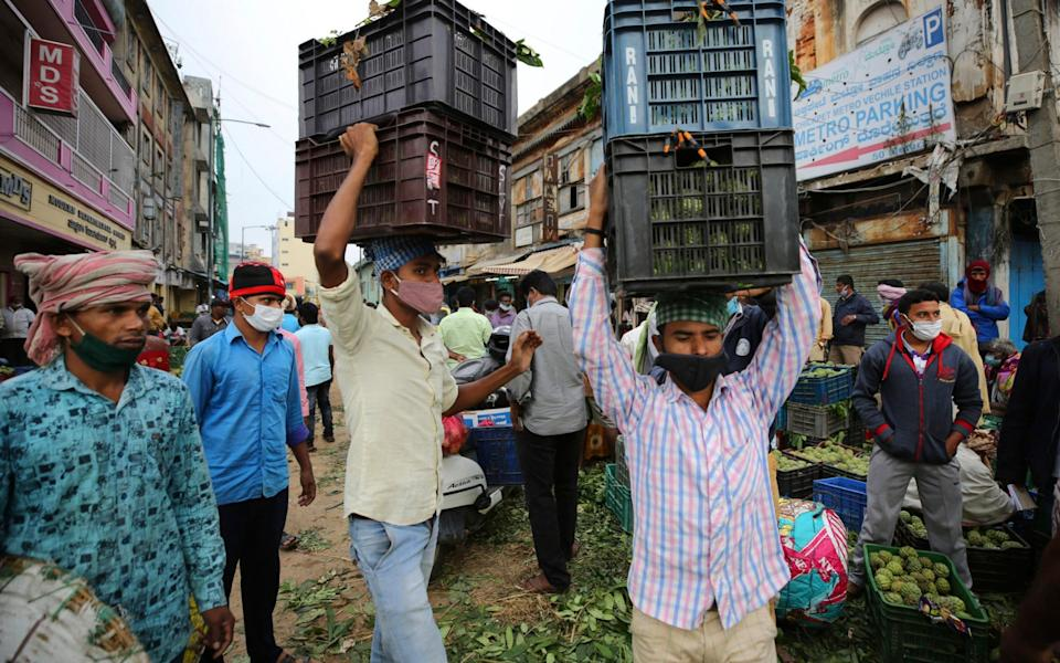 Daily wage laborers wearing face masks as a precaution against the coronavirus carry fruit baskets at a wholesale market in Bengaluru, India - AP