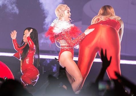 Miley Cyrus slaps her dancer's butt during the first concert of her Bangerz Tour on Feb. 14