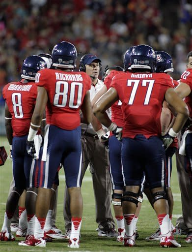Arizona's head coach Rich Rodriguez, center, talks to his players on the sidelines during a timeout against Oklahoma State the first half of an NCAA college football game at Arizona Stadium in Tucson, Ariz., Saturday, Sept. 8, 2012. (AP Photo/John Miller)