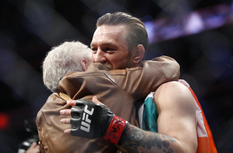 """Conor McGregor, right, embraces Jerry Cerrone, the grandmother of Donald """"Cowboy"""" Cerrone, after a UFC 246 welterweight mixed martial arts bout, Saturday, Jan. 18, 2020, in Las Vegas. (AP Photo/John Locher)"""