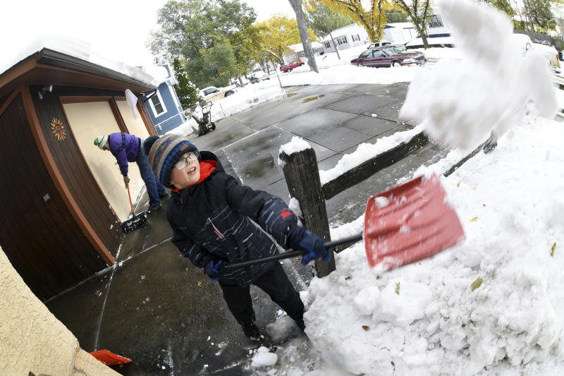Garrett Simons, 7, helps his grandfather, Dave Salter, shovel snow from the driveway and sidewalks from his home, Friday, Oct. 11, 2019 in Bismarck, N.D. North Dakota Gov. Doug Burgum on Friday activated the state's emergency plan due to what he called a crippling snowstorm that closed major highways and had farmers and ranchers bracing for the potential of huge crop and livestock losses. (Mike McCleary/The Bismarck Tribune via AP)