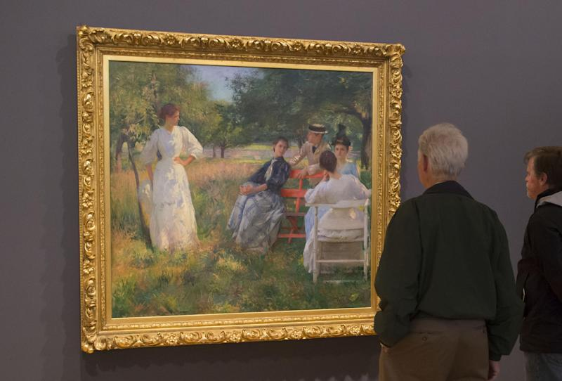 "People look at the painting of American painter Edmund Tarbell, 1862-1938, in the Orchard, 1891, during the exhibition, ""American Impressionism: A New Vision"", at the Impressionist museum in Giverny, 70 kms (45 mls) north west of Paris, on Friday, March 28, 2014. A new exhibit at Normandy's Impressionism Museum tells for the first time the little-known story of American Impressionism from where it all began _ at the picturesque water lily-filled Giverny gardens of Claude Monet that Americans colonized for three decades. (AP Photo/Michel Euler)"
