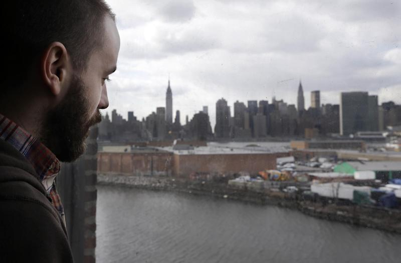 """Aaron Myers, an employee of North Sculpture Company peers out his fourth-story window overlooking Newtown Creek, a federal Superfund site opposite midtown Manhattan's skyline in New York, Wednesday, Feb. 20, 2013. A regional administrator for the federal Environmental Protection Agency, says Newtown Creek """"is one of the most polluted urban water bodies in the world."""" (AP Photo/Kathy Willens)"""