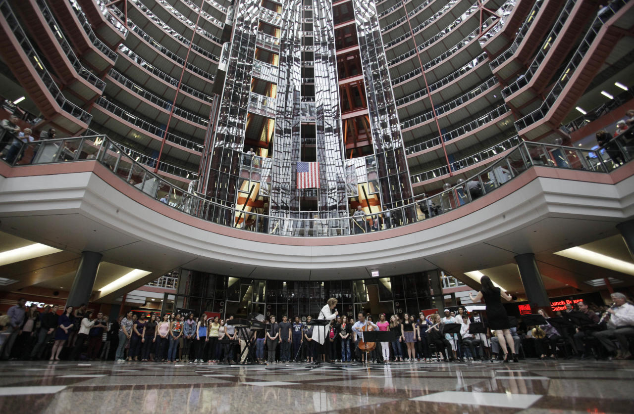 World-famous cellist Yo-Yo Ma and famed soprano Renee Fleming perform with a choir of dozens of high school students in the rotunda of the State of Illinois building, the James R. Thompson Center, Monday, March 19, 2012, in Chicago. The Monday afternoon performance was to promote the Chicago Symphony Orchestra's Citizen Musician initiative. The Lyric Opera of Chicago also sponsored the event and Illinois Gov. Pat Quinn attended. (AP Photo/Kiichiro Sato)