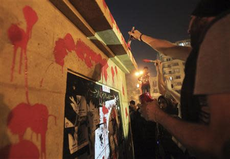Demonstrators deface a new memorial in the centre of Tahrir Square as protesters hold rallies, in Cairo