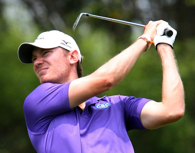 Chris Wood of Britain watches his fairway shot during the third round of Thailand Open Golf Championship at Thana City Golf and Sports Club on the outskirts of Bangkok, Thailand Saturday, March 16, 2013. (AP Photo/Apichart Weerawong)