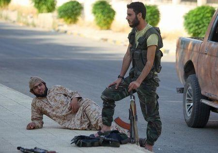 """Fighters from a coalition of rebel groups called """"Jaish al Fateh"""" rest with their weapons near Zeyzoun thermal station in al-Ghab plain in the Hama countryside"""
