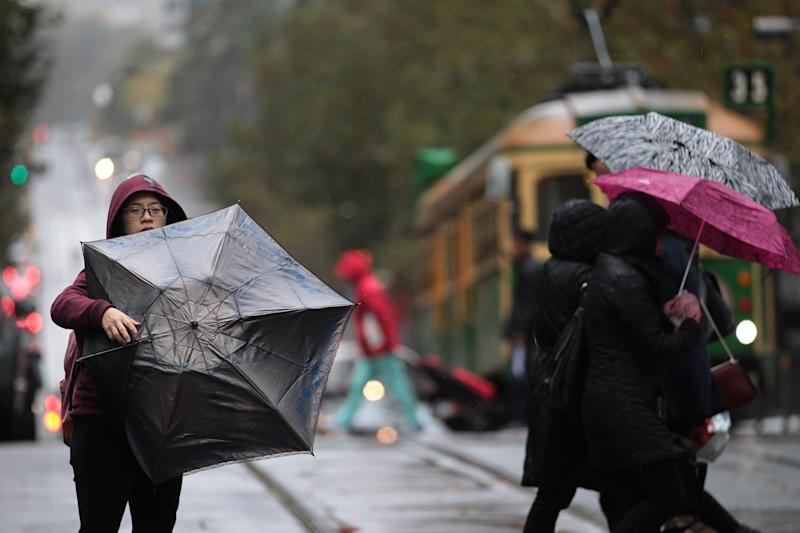A woman struggles with her umbrella in the Melbourne CBD in May 2018. Victoria is set for two cold fronts and heavy winds this week.