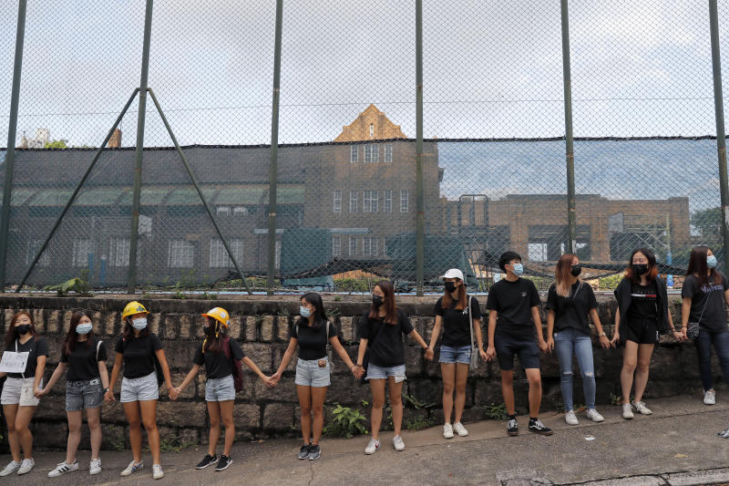 People form human chain outside the Maryknoll Convent School in Hong Kong, Friday, Sept. 6, 2019. Hong Kong leader Carrie Lam said Thursday that the decision to withdraw an extradition bill that sparked months of demonstrations in the semi-autonomous Chinese territory was her government's own initiative to break the impasse, and not Beijing's directive. (AP Photo/Kin Cheung)