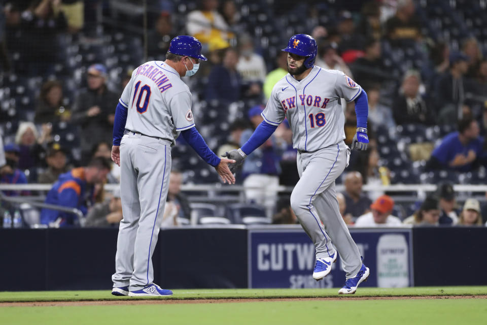 New York Mets' Jose Peraza (18) slaps hands with third base coach Gary Disarcina (10) as he rounds third base after hitting a solo home run during the fifth inning of the team's baseball game against the San Diego Padres on Saturday, June 5, 2021, in San Diego. (AP Photo/Derrick Tuskan)