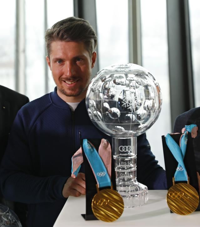 Austrian overall ski World Cup champion Marcel Hirscher poses with a trophy and Olympic medals at a news conference in Vienna, Austria, March 21, 2018. REUTERS/Leonhard Foeger