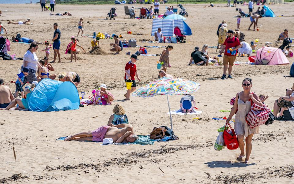 Sunbathers made the most of the mini heatwave in New Brighton, Wirral, on the the hottest day of the year (PA Wire)