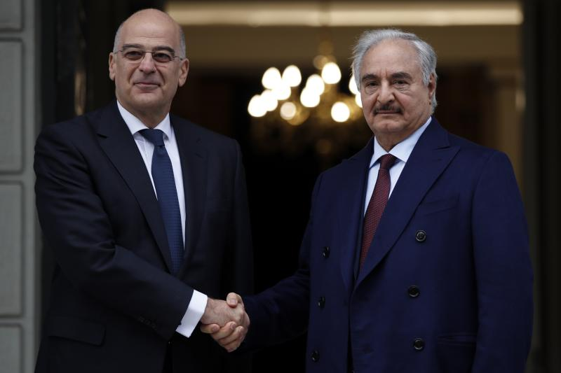 Libyan Gen. Khalifa Hifter, right, and Greek Foreign Minister Nikos Dendias shake hands before their meeting in Athens, Friday, Jan. 17, 2020. The commander of anti-government forces in war-torn Libya has begun meetings in Athens in a bid to counter Turkey's support for his opponents. (AP Photo/Thanassis Stavrakis)