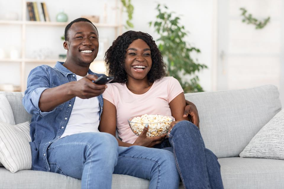 Happy african american family of two watching movie together at home, laughing and eating popcorn, copy space