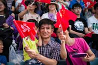 People react as they raise Chinese and Hong Kong flags during the open day of the Chinese People's Liberation Army (PLA) Navy Base at Stonecutter Island in Hong Kong on July 1, 2016