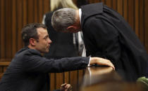 Olympic and Paralympic track star Oscar Pistorius (L) cries as he chats to his lawyer Barry Roux during his trial for the murder of his girlfriend Reeva Steenkamp, at the North Gauteng High Court in Pretoria March 10, 2014. Pistorius is on trial for murdering his girlfriend Reeva Steenkamp at his suburban Pretoria home on Valentine's Day last year. He says he mistook her for an intruder. REUTERS/Siphiwe Sibeko (SOUTH AFRICA - Tags: CRIME LAW SPORT ATHLETICS)
