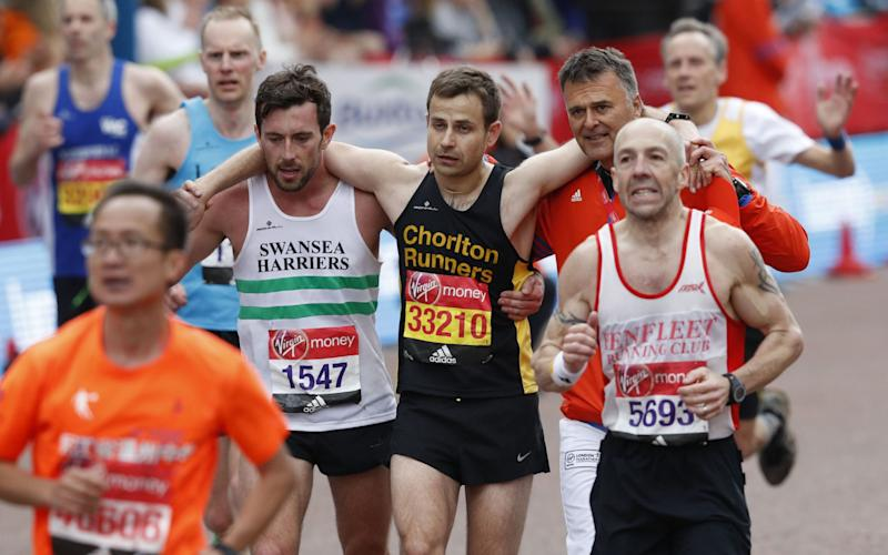 Matthew Rees helped another runner over the line - Credit: ADRIAN DENNIS/AFP