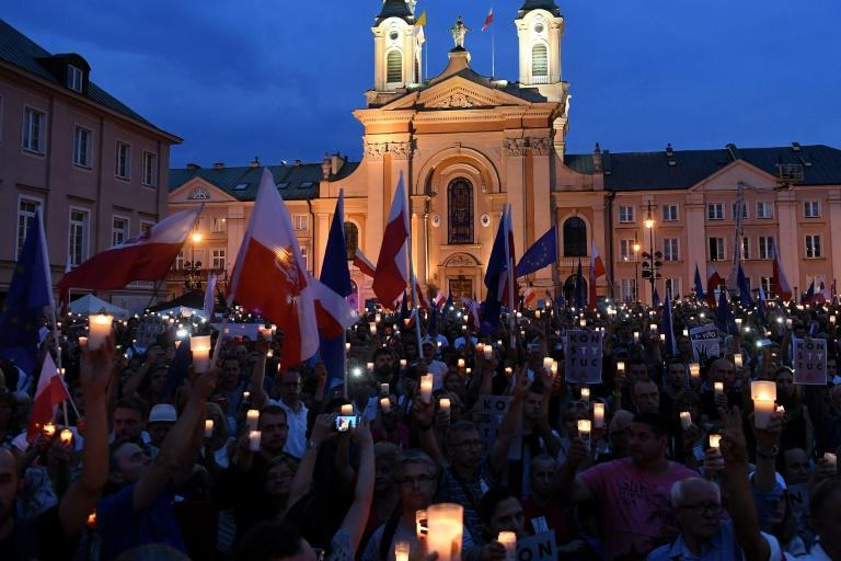 People hold candles and Polish national flags as they take part in demonstration in front of the Polish Supreme Court on July 23, 2017 in Warsaw to protest against a bill changing the judiciary system
