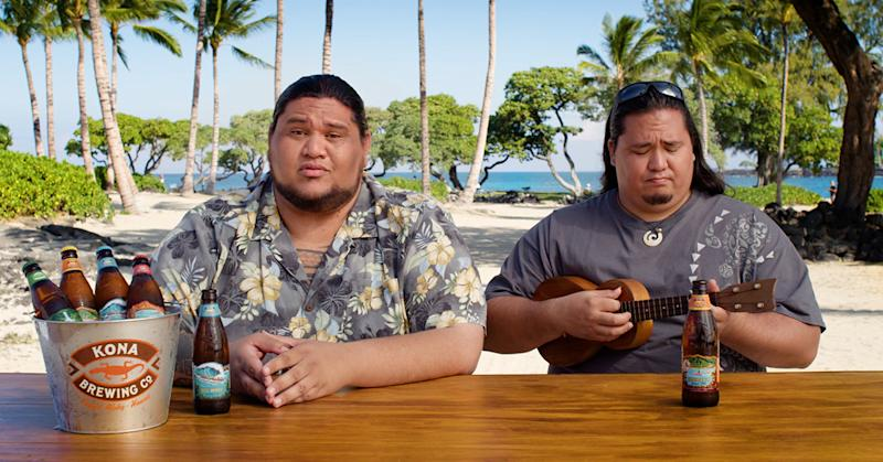 Two men, one with a ukulele, and Kona beer