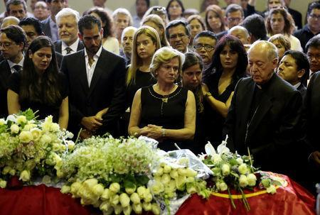Archbishop Juan Luis Cipriani (R), Pilar Nores (C), former wife of Peru's former President Alan Garcia, family members and friends gather near the coffin holding Garcia's body during his wake, after he fatally shot himself on Wednesday, in Lima, Peru April 18, 2019. REUTERS/Guadalupe Pardo