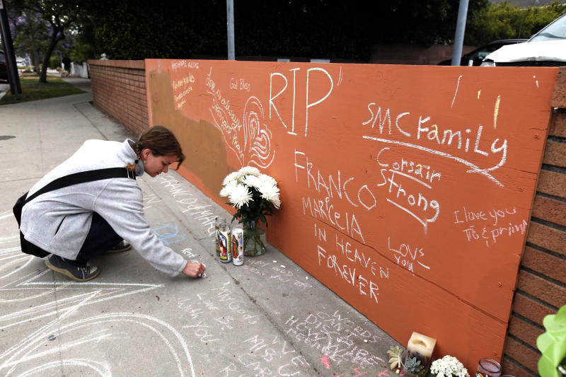 Sonya Geis writes a note at a memorial at Santa Monica College, Monday, June 10, 2013, in Santa Monica, Calif. Santa Monica College reopened under extra security Monday except for the library, where police shot and killed a heavily armed gunman after a rampage that left five people dead on Friday.  Students who fled Friday would be able to resume final examinations and retrieve backpacks, cars and other belongings, according to the college website. (AP Photo/Nick Ut)